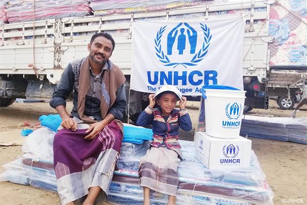 UNHCRの支援物資を受け取るイエメン避難民の父子