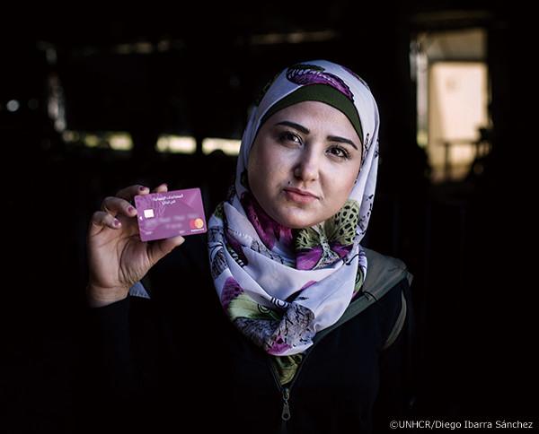 現金給付用カードを手にする難民