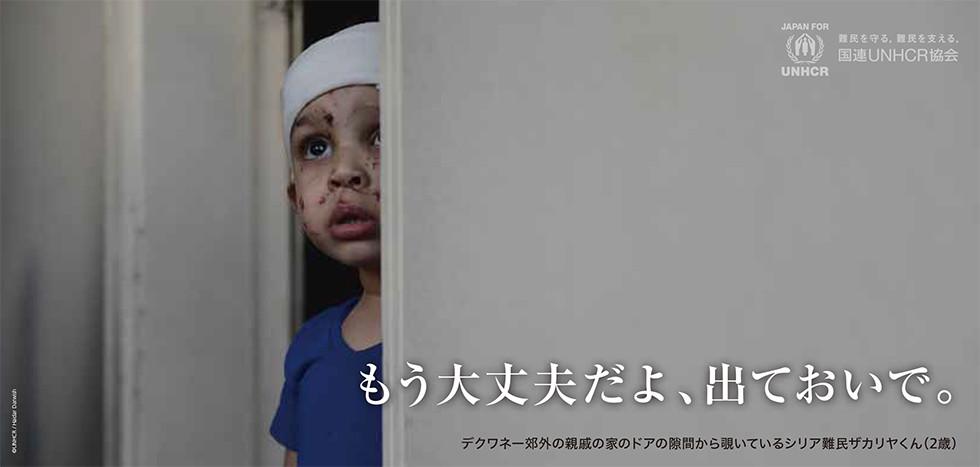 大丈夫だよ、出ておいで。デクワネー郊外の親戚の家のドアの隙間から覗いているシリア難民ザカリヤくん(2歳) 国連UNHCR協会