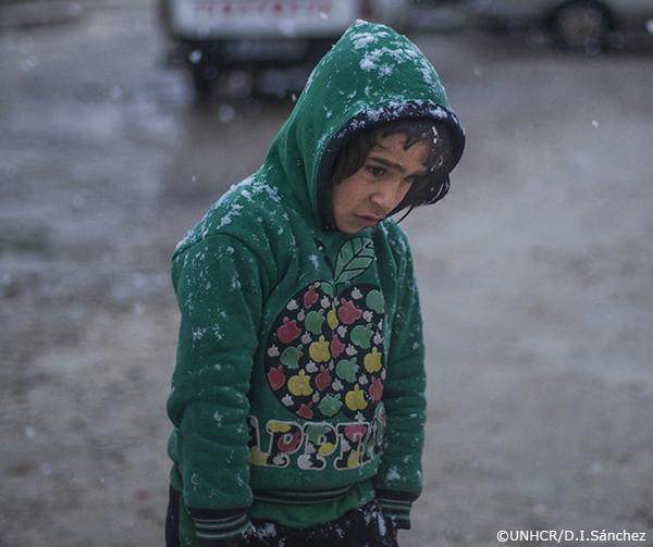 雪の中を歩く難民の少年
